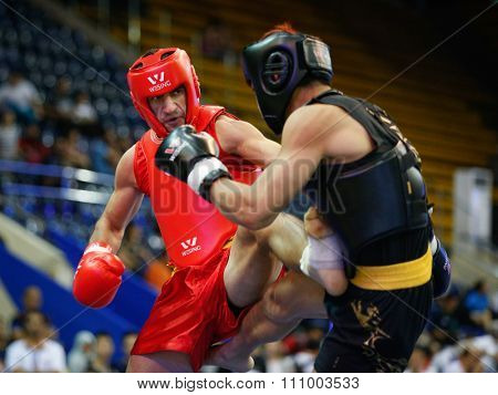 JAKARTA, INDONESIA - NOVEMBER 15, 2015: Elie Bou Gebrael of Lebanon (red) fights Praveen Biskawkarma of Hong Kong (black) in the men's 70kg Sanda event at the 13th World Wushu Championship 2015.