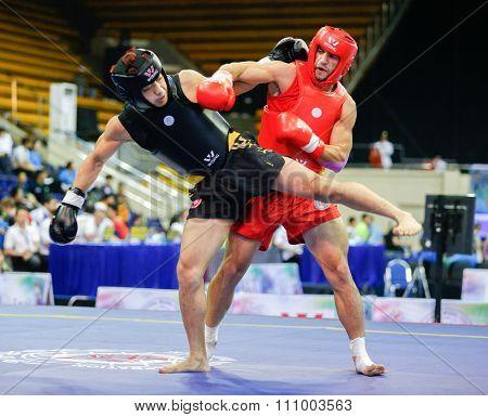 JAKARTA, INDONESIA - NOVEMBER 15, 2015: Elie Bou Gebrael of Lebanon (red) fights Praveen Biskawkarma of Hong Kong (black) in the men's 70kg Sanda event at the 13th World Wushu Championship 2015.