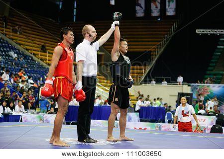 JAKARTA, INDONESIA - NOVEMBER 15, 2015: Puja Riyaya of Indonesia (red) loses to Van Tai Nguyen of Vietnam (black) in the men's 70kg Sanda event at the 13th World Wushu Championship 2015 in Jakarta.