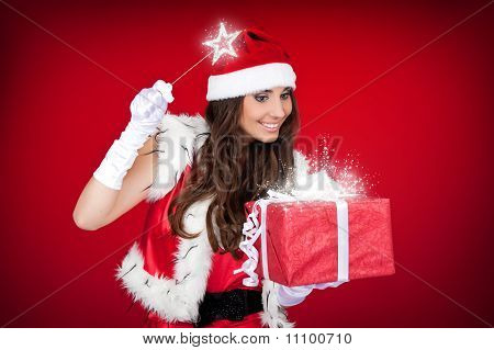 Santa Girl Adding Little Magic To Christmas Present