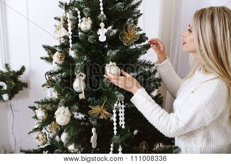 Beautiful Young Girl Decorates The Christmas Tree