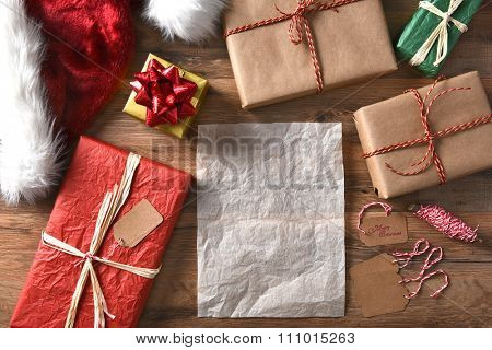 Overhead view of wrapped Christmas presents on a rustic wood table with string, gift tags, and Santa hat. Horizontal format with a blank sheet of paper.
