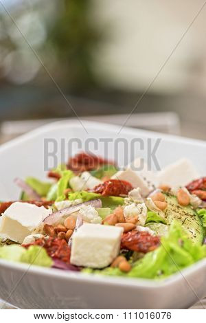 Salad feta cheese lettuce sausage cucumbers and pine nuts