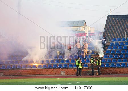 fans on tribune with fires and police