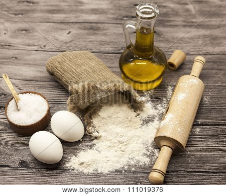 Wheat flour in a canvas bag, the olive oil in a glass carafe, a large salt shaker wood, raw eggs, a wooden rolling pin: set for making homemade bread dough on a beautiful dark wooden background.