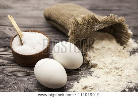 Wheat flour in a canvas bag, a large salt shaker wood, raw eggs: set for making homemade bread dough on a beautiful dark wooden background.