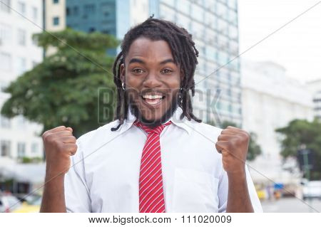Cheering African American Businessman With Dreadlocks In The City