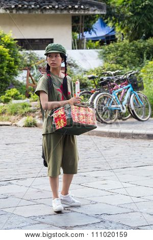 Yangshuo, China - Circa July 2015: Chinese Young Pioneer Girl Sells Food Or Souvenirs On The Streets
