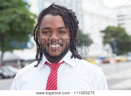 Laughing African American Businessman With Dreadlocks In The City
