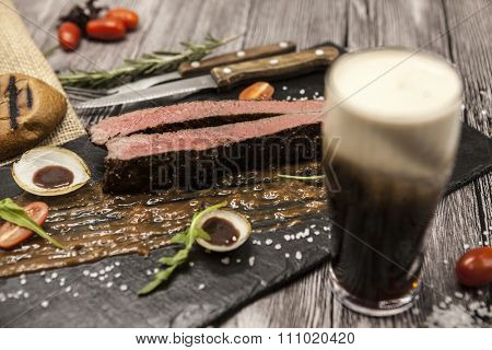 Ribeye steak from marble beef meat with vegetables and barbecue sauce. Served on a plate of black stone with fork and knife and beer.