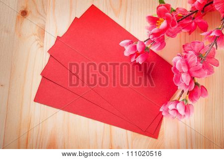 Chinese new year festival decorations, blank copy space on ang pow or red packet and plum blossom on vintage wooden background.