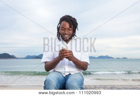 African American Guy With Dreadlocks And White Shirt Typing Message