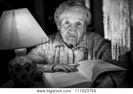 An elderly woman reading a book with night lamp. Black and white photo.