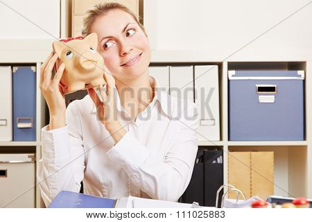 Smiling business woman in office at her desk holding a piggy bank