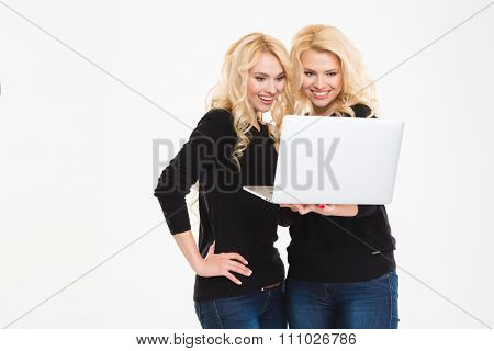 Portrait of a happy sisters twins using laptop computer isolated on a white background