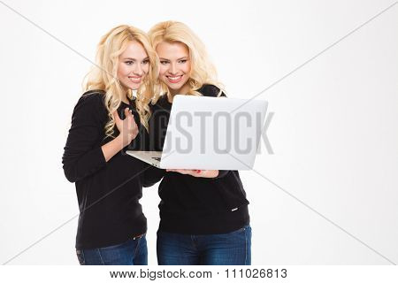 Portrait of a smiling sisters twins using laptop computer isolated on a white background