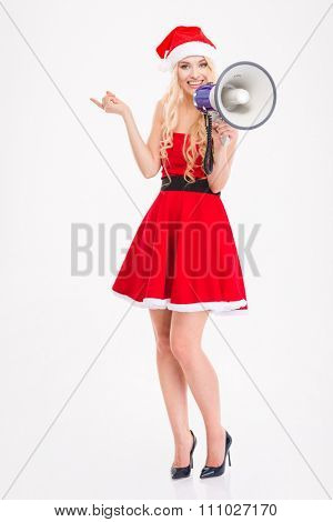 Full length of joyful attractive blonde woman in santa claus dress and hat with megaphone pointing away over white background