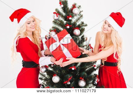 Two pretty blonde sisters twins in red santa claus costumes and hats holding one gift near Christmas tree over white background