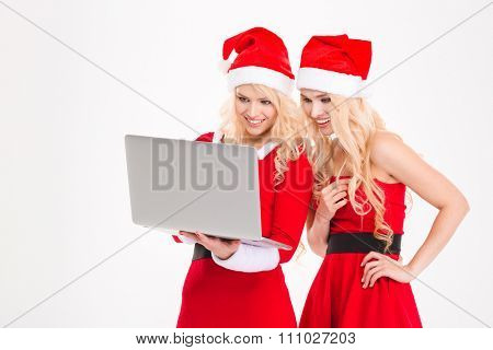 Two attractive young sisters twins in red santa claus costumes and hats using laptop over white background