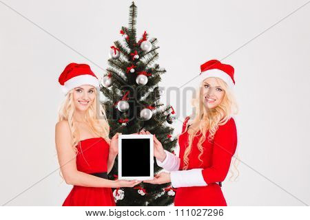 Two attrative young sisters twins in red santa claus dresses and hats showing laptop with blank screen near Christmas tree over white background