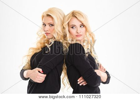 Portrait of a young serious sisters twins standing back to back with arms folded isolated on a white background
