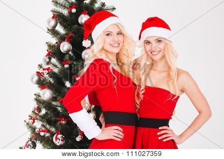 Two beautiful happy sisters twins in red santa claus costumes and hats standing near Christmas tree over white background