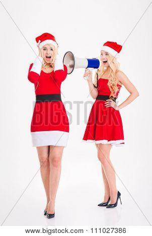 Attractive amusing sisters twins in santa claus costumes and hat speaking in loudspeaker over white background