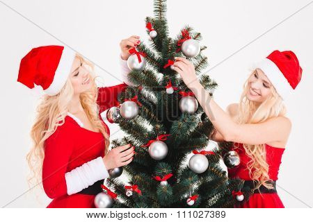 Attractive smiling blonde sisters twins in red santa claus clothes and hats decorating Christmas tree over white background