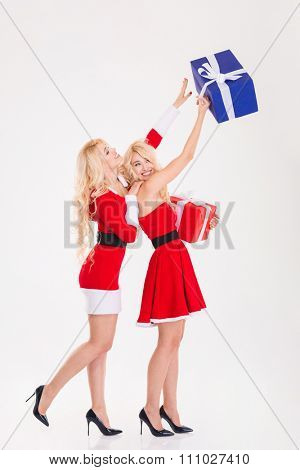 Full length of two playful sisters twins in dresses of santa claus having fun and getting presents over white background
