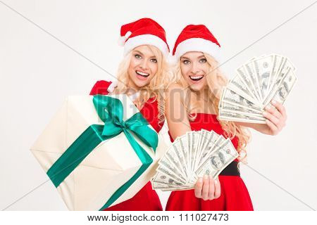 Excited beautiful sisters twins in santa claus costumes and hats showing money and gift over white background