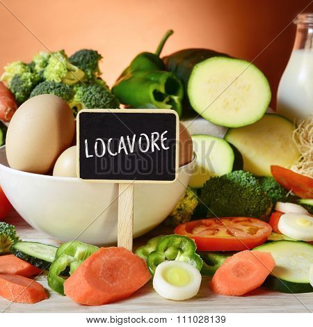 closeup of a signboard with the english word locavore, for a person interested in eating locally produced food, on a table full of raw vegetables, a bowl with chicken eggs and a bottle with milk