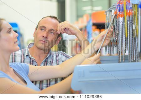 Lady choosing drill bit, man looking sceptical