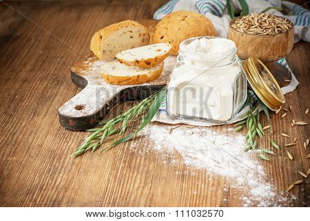 Oat flour, oatmeal bread and ears of green oats on a wooden background for home baking
