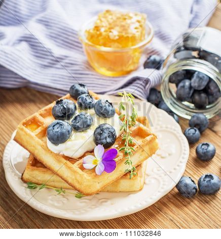 Belgian golden waffles for breakfast with fresh berries and flower honey on wooden background. The c