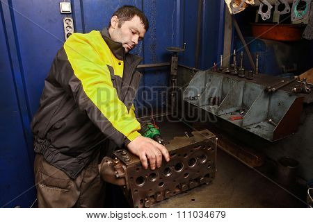 Young Car Mechanic Cleans Channels Of The Cylinder Head Engine.