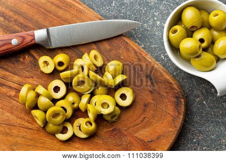 sliced green olives on cutting board
