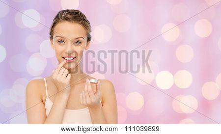 beauty, people and lip care concept - smiling young woman applying lip balm to her lips over pink lights background
