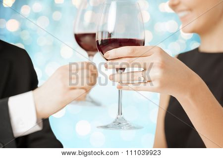 people, holidays, marriage and celebration concept - happy engaged couple clinking wine glasses over blue holidays lights background