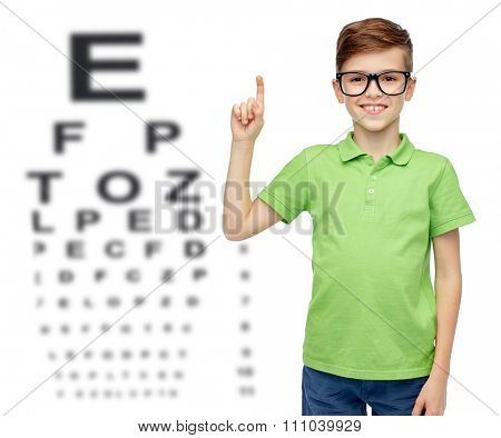 childhood, vision, eyesight and people concept - happy smiling boy in green polo t-shirt in eyeglasses pointing finger up over eye chart background