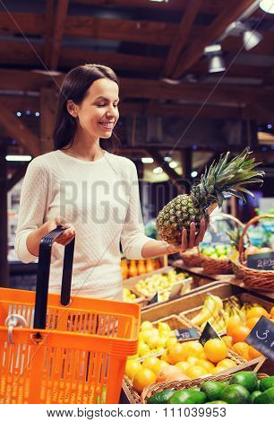 sale, shopping, consumerism and people concept - happy young woman with food basket in market