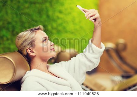 people, beauty, lifestyle, technology and relaxation concept - beautiful young woman in white bath robe taking selfie with smartphone at spa