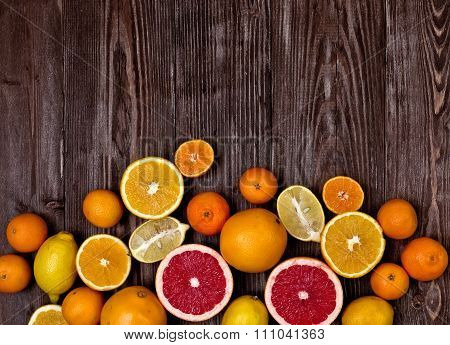 Fresh Fruits Citruses On A Dark Wooden Background. Raw And Vegetarian Eating Frame.