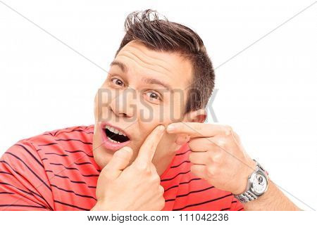 Young man squeezing a pimple on his cheek and looking at the camera isolated on white background