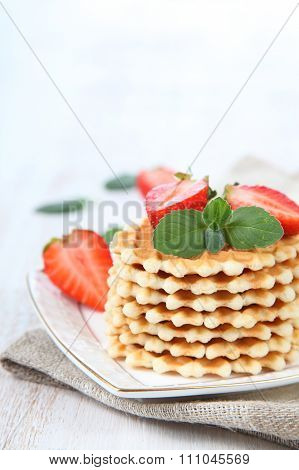 Waffles With Strawberries On A Wooden Table
