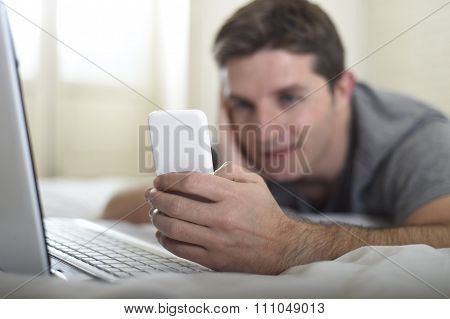 Young Attractive Man Lying On Bed Or Couch Using Mobile Phone And Computer Laptop Internet Addict
