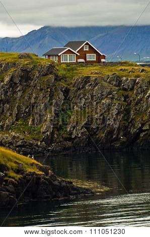 House on top of a cliff in west Icelandic fjord near Stykkisholmur harbor