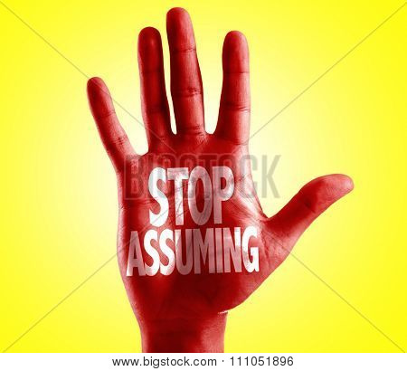 Stop Assuming written on hand with yellow background