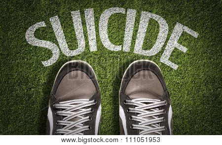 Top View of Sneakers on the grass with the text: Suicide