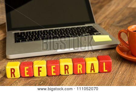 Referral written on a wooden cube in a office desk