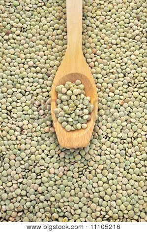 Wooden spoon and dried green lentils